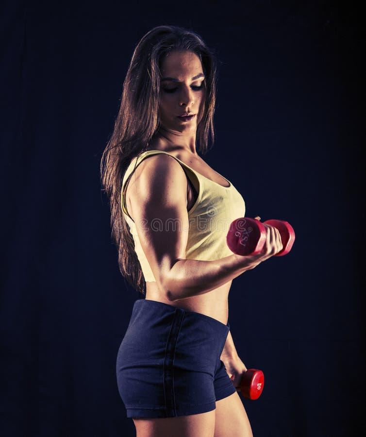 Mujer joven fuerte que hace rizos del bíceps foto de archivo