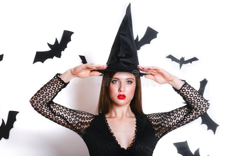 Mujer joven gótica feliz en el traje de Halloween de la bruja con el sombrero que se coloca y que sonríe sobre el fondo blanco fotos de archivo libres de regalías