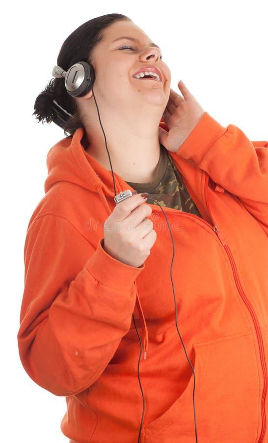 Mujer joven gorda con los auriculares y el jugador mp3 imagenes de archivo