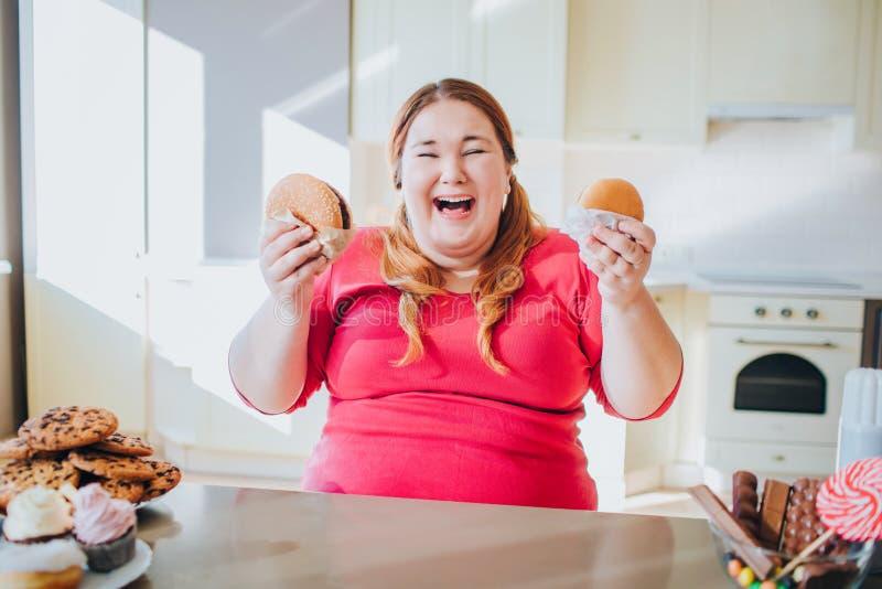 Mujer joven gorda en la cocina que sienta y que come la comida basura Risa emocionada feliz del modelo del tamaño extra grande So fotos de archivo libres de regalías
