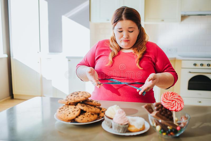 Mujer joven gorda en la cocina que sienta y que come la comida dulce Mirada seria confusa del modelo del tamaño extra grande en l imagen de archivo