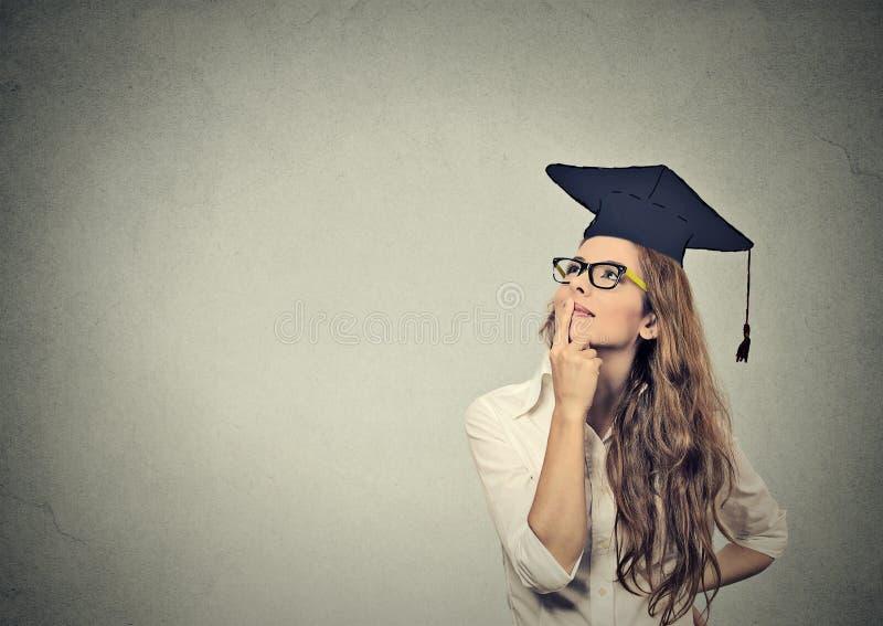 Mujer joven graduada pensativa del estudiante graduado en el vestido del casquillo que mira para arriba de pensamiento imágenes de archivo libres de regalías