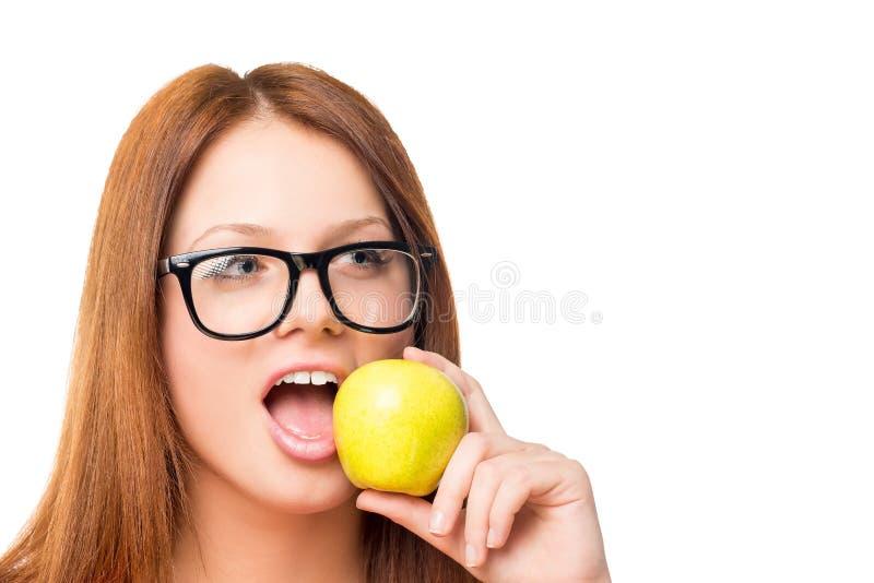 Mujer joven hambrienta con los vidrios que muerde una manzana verde imagenes de archivo