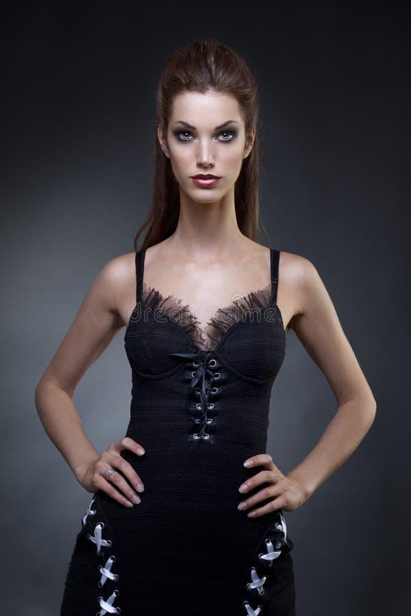 Mujer joven hermosa adentro en un vestido oscuro foto de archivo