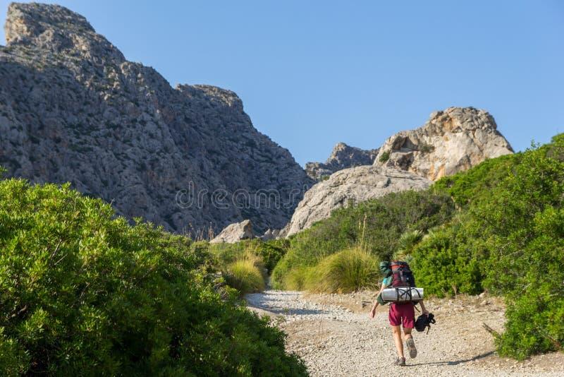 Mujer joven, hermosa, adolescente con la mochila que camina en montañas imagenes de archivo