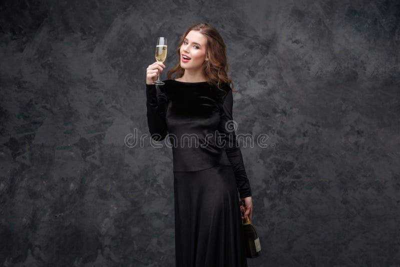 Mujer joven hermosa alegre que sostiene la botella y el vidrio de champán fotografía de archivo