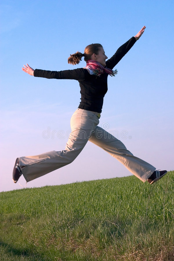 Mujer joven hermosa apta que salta en el cielo fotografía de archivo