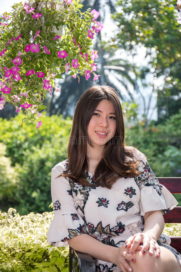 Mujer joven hermosa asiática que se sienta en banco en jardín al aire libre imagen de archivo libre de regalías