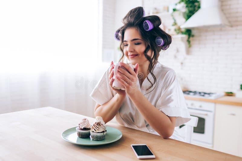 Mujer joven hermosa atractiva agradable en cocina Taza del control en manos y sueño Ojos cerrados Crepes en la placa Teléfono enc fotografía de archivo libre de regalías
