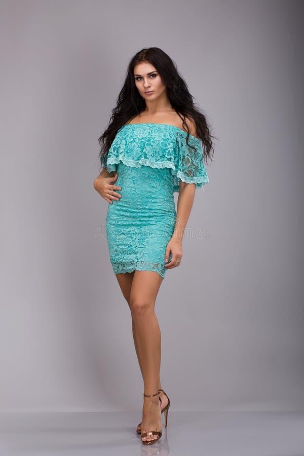Mujer joven hermosa atractiva en un vestido azul en un fondo gris imagen de archivo libre de regalías