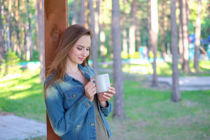 Mujer joven hermosa, café para llevar de consumición de la taza, al aire libre en verano , fotografía de archivo libre de regalías