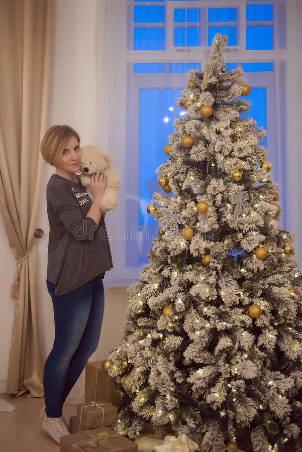 Mujer joven hermosa cerca del árbol de navidad foto de archivo