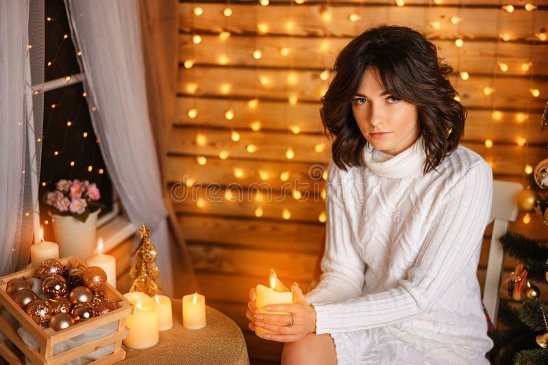Mujer joven hermosa cerca del árbol de navidad en suéter blanco, para Año Nuevo que espera acogedor y días de fiesta de la Navida fotografía de archivo