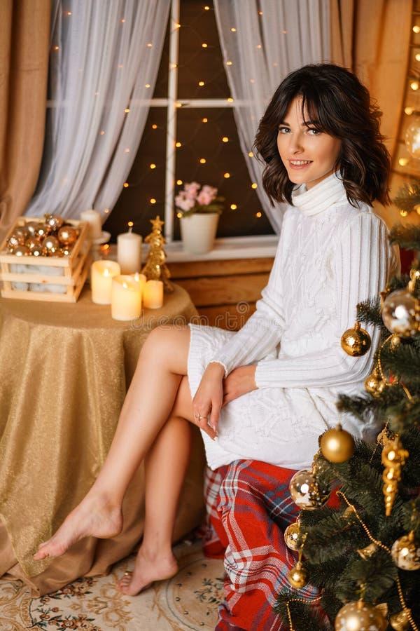 Mujer joven hermosa cerca del árbol de navidad en suéter blanco, para Año Nuevo que espera acogedor y días de fiesta de la Navida fotos de archivo