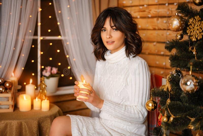 Mujer joven hermosa cerca del árbol de navidad en suéter blanco, para Año Nuevo que espera acogedor y días de fiesta de la Navida fotos de archivo libres de regalías