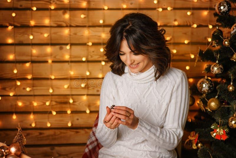 Mujer joven hermosa cerca del árbol de navidad en suéter blanco, para Año Nuevo que espera acogedor y días de fiesta de la Navida imagen de archivo