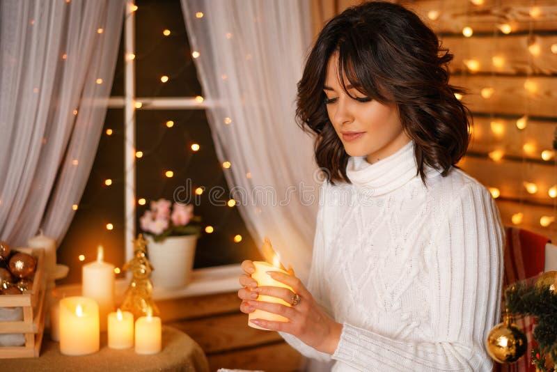 Mujer joven hermosa cerca del árbol de navidad en suéter blanco, para Año Nuevo que espera acogedor y días de fiesta de la Navida fotografía de archivo libre de regalías
