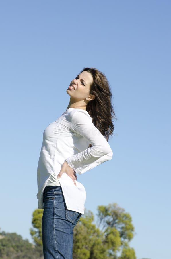 Mujer joven hermosa con dolor de espalda fotos de archivo