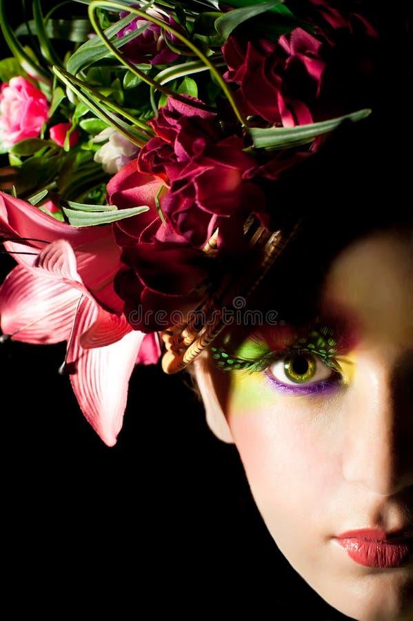 Mujer joven hermosa con el casquillo creativo de la flor fotografía de archivo
