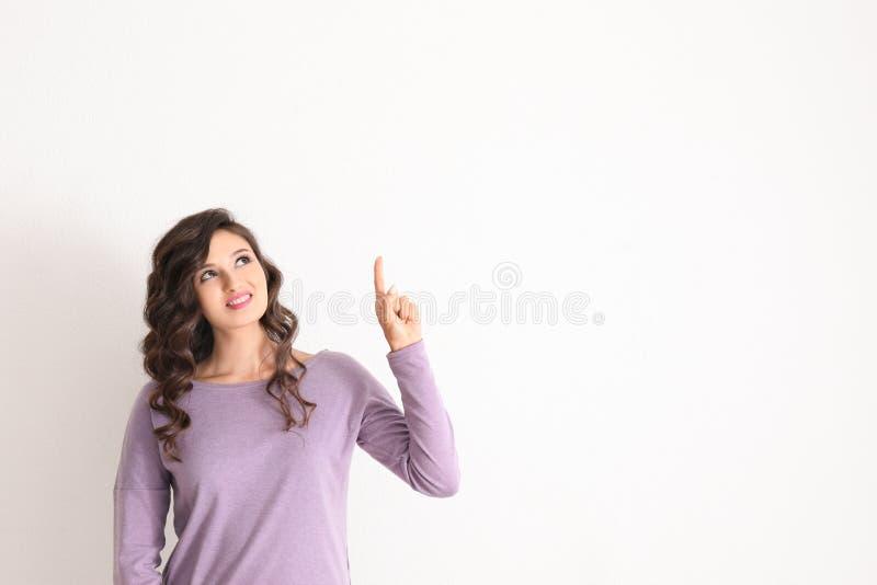 Mujer joven hermosa con el dedo índice aumentado en fondo ligero fotos de archivo libres de regalías