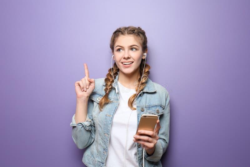 Mujer joven hermosa con el dedo índice aumentado que escucha la música en fondo del color imagen de archivo libre de regalías
