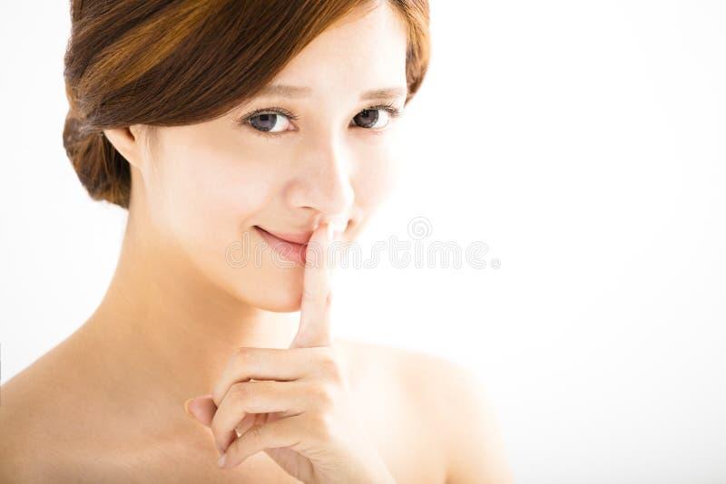 Mujer joven hermosa con el dedo en los labios foto de archivo