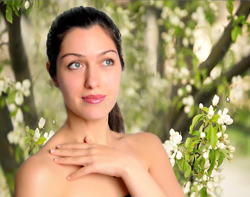 Mujer joven hermosa con el fondo de la flor de la primavera imagenes de archivo