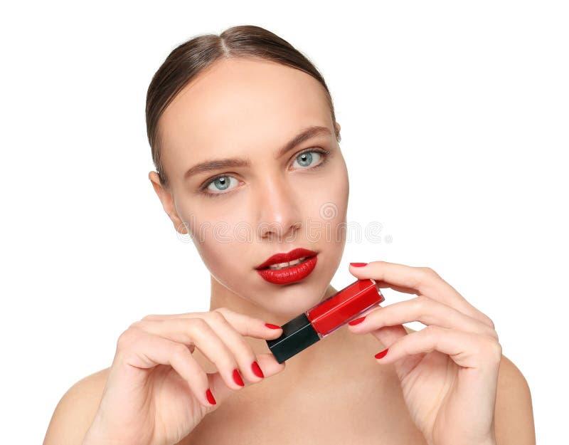 Mujer joven hermosa con el maquillaje profesional que sostiene la barra de labios brillante en el fondo blanco fotografía de archivo libre de regalías