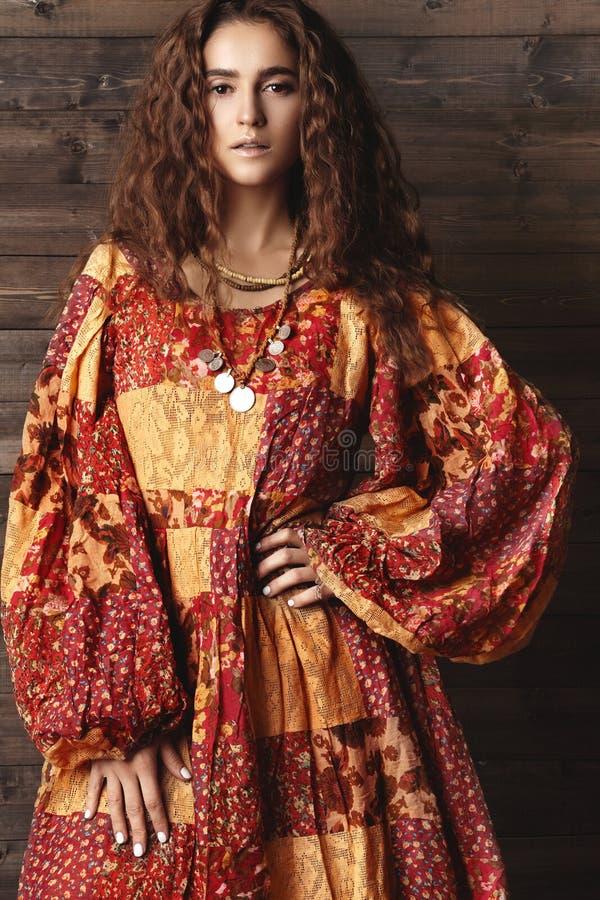 Mujer joven hermosa con el peinado rizado largo, joyería de la moda con el pelo moreno Ropa india del estilo, vestido largo fotos de archivo