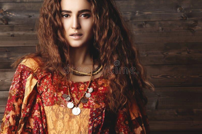 Mujer joven hermosa con el peinado rizado largo, joyería de la moda con el pelo moreno Ropa india del estilo, vestido largo imagenes de archivo