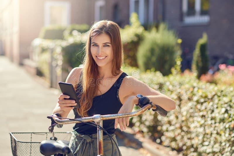Mujer joven hermosa con el pelo largo en retrato delantero de medio cuerpo al aire libre en la situación de la ciudad que se incl fotografía de archivo libre de regalías
