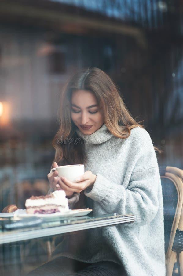 Mujer joven hermosa con el pelo largo marrón que se sienta en el café, drin imágenes de archivo libres de regalías
