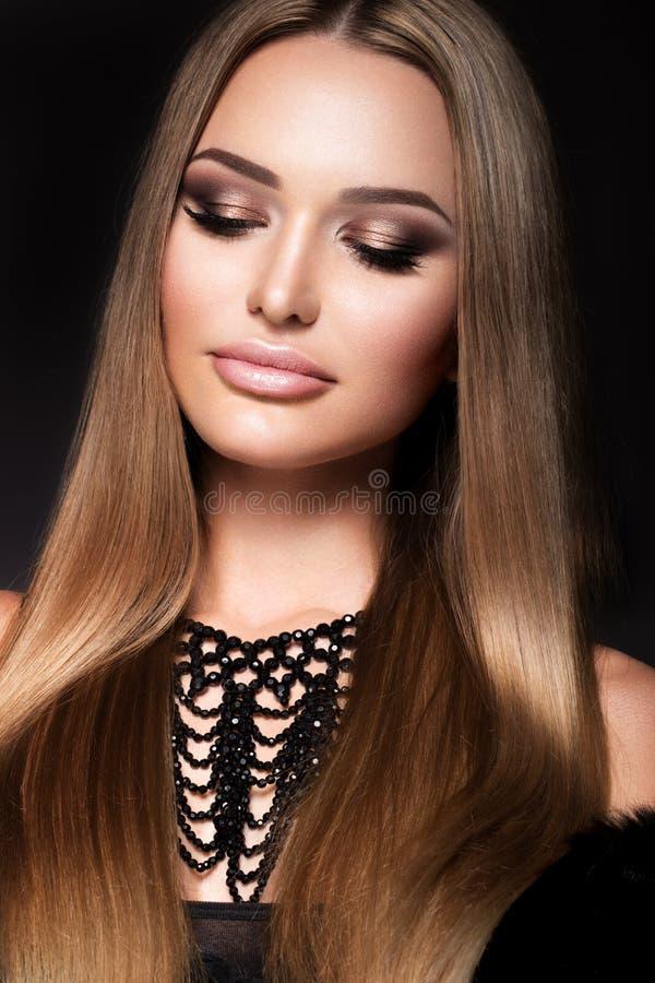 Mujer joven hermosa con el pelo largo que presenta en fondo negro foto de archivo