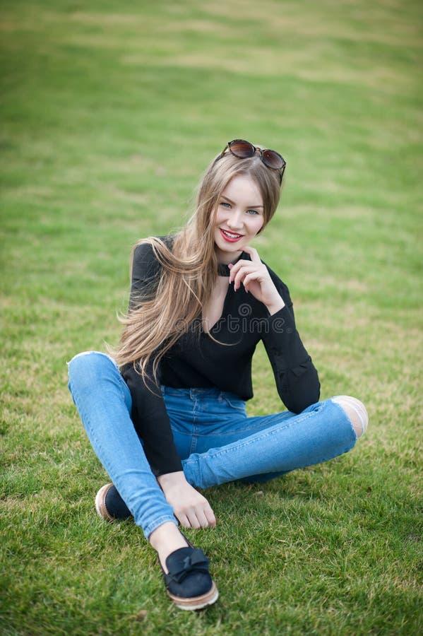 Mujer joven hermosa con el pelo largo que se sienta en la hierba verde fotos de archivo libres de regalías