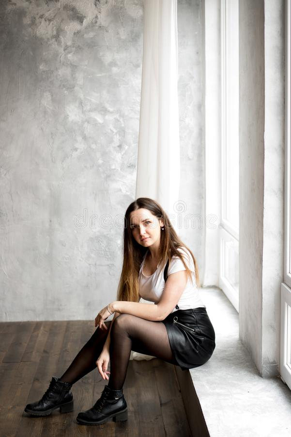 Mujer joven hermosa con el pelo largo que se sienta en travesaño de la ventana en sitio con la pared de la turquesa Ella es de mi foto de archivo