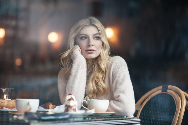 Mujer joven hermosa con el pelo largo rubio que se sienta solamente en el caf imagenes de archivo