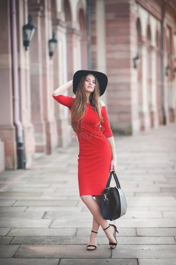 Mujer joven hermosa con el pelo largo, sombrero negro, panier foto de archivo