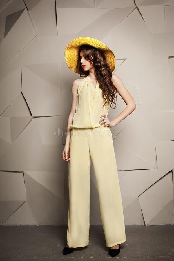 Mujer joven hermosa con el pelo marrón largo rizado que se coloca en sombrero y mono amarillos fotografía de archivo libre de regalías
