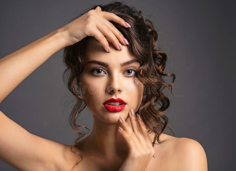 Mujer joven hermosa con el pelo marr?n rizado largo foto de archivo
