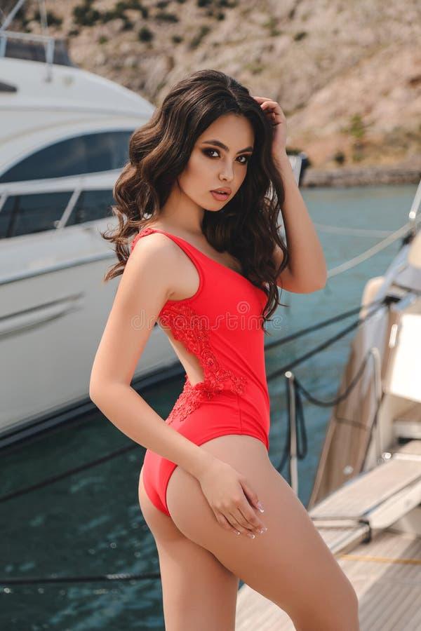 Mujer joven hermosa con el pelo oscuro en el traje de natación elegante po imagenes de archivo