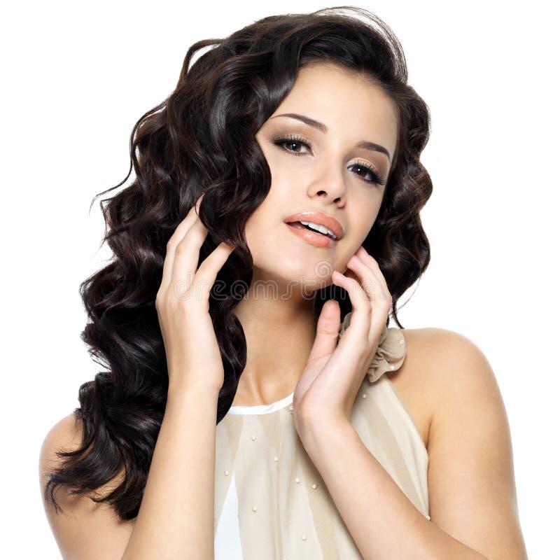 Mujer joven hermosa con el pelo rizado largo de la belleza. imagen de archivo