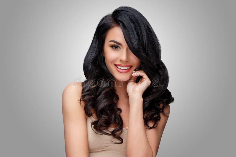 Mujer joven hermosa con el pelo rizado sano limpio fotografía de archivo