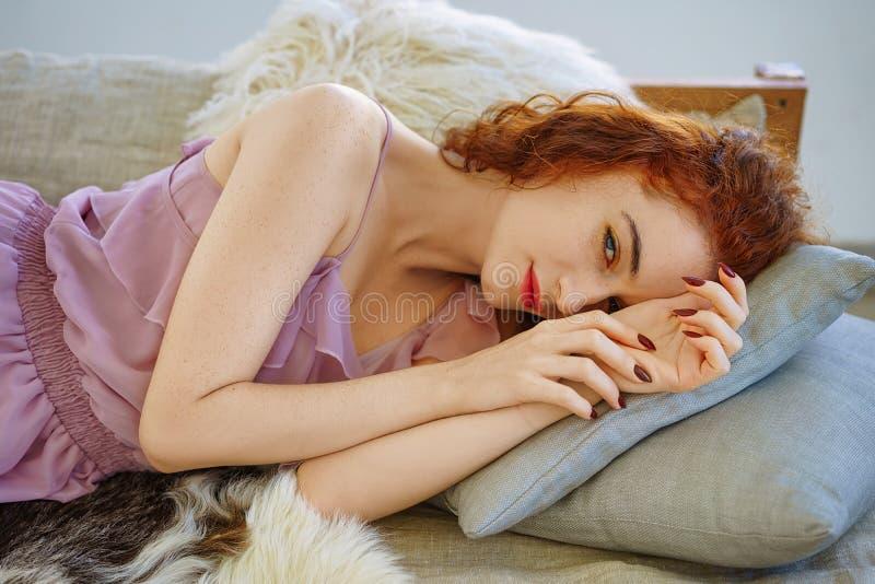Mujer joven hermosa con el pelo rojo que miente en el sofá fotos de archivo