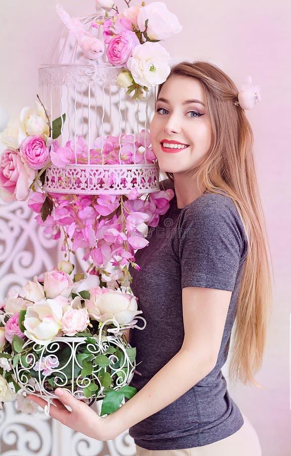 Mujer joven hermosa con el pelo rubio largo, ojos azules, jaula floreciente, camiseta que lleva imagenes de archivo