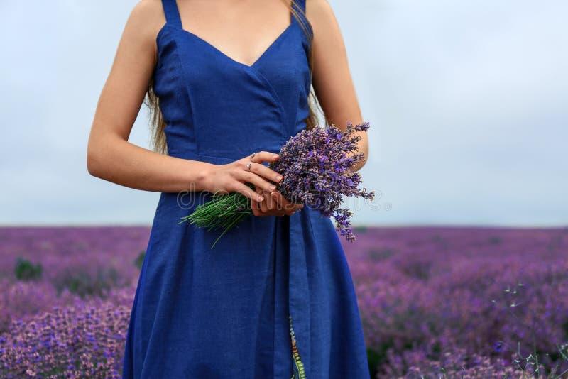 Mujer joven hermosa con el ramo de lavanda en campo el día de verano fotografía de archivo