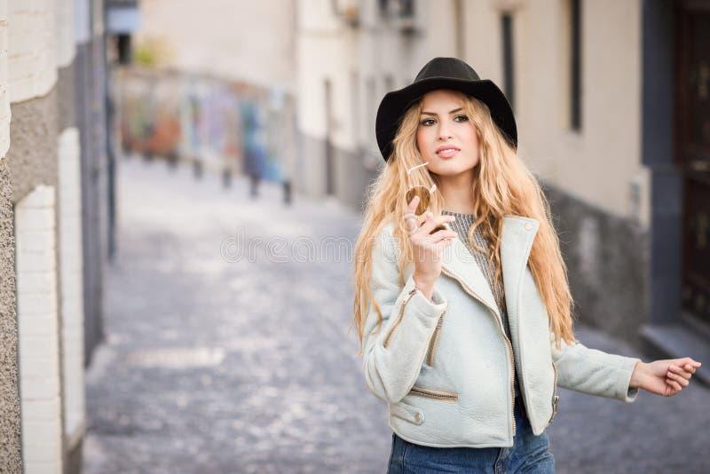 Mujer joven hermosa con el sombrero que lleva del pelo rizado imagenes de archivo