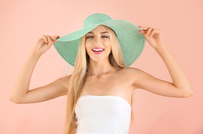 Mujer joven hermosa con la barra de labios y el sombrero rosados brillantes en fondo ligero imagen de archivo