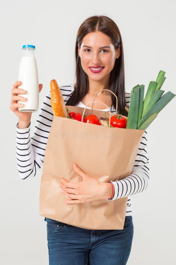 Mujer joven hermosa con la botella de leche que sostiene los ultramarinos fotos de archivo libres de regalías