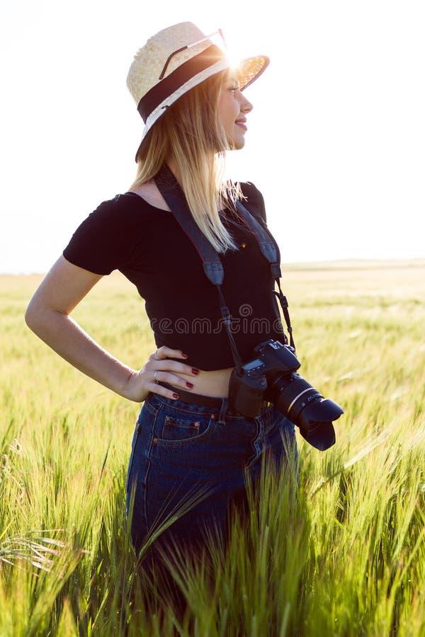 Mujer joven hermosa con la cámara digital que toma las fotos en un campo foto de archivo libre de regalías