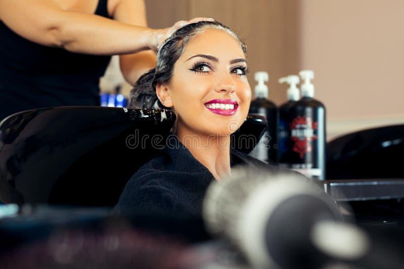 Mujer joven hermosa con la cabeza que se lava del peluquero en el salón de pelo foto de archivo